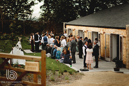 Wedding guests enjoy an evening drink outside our rustic barn