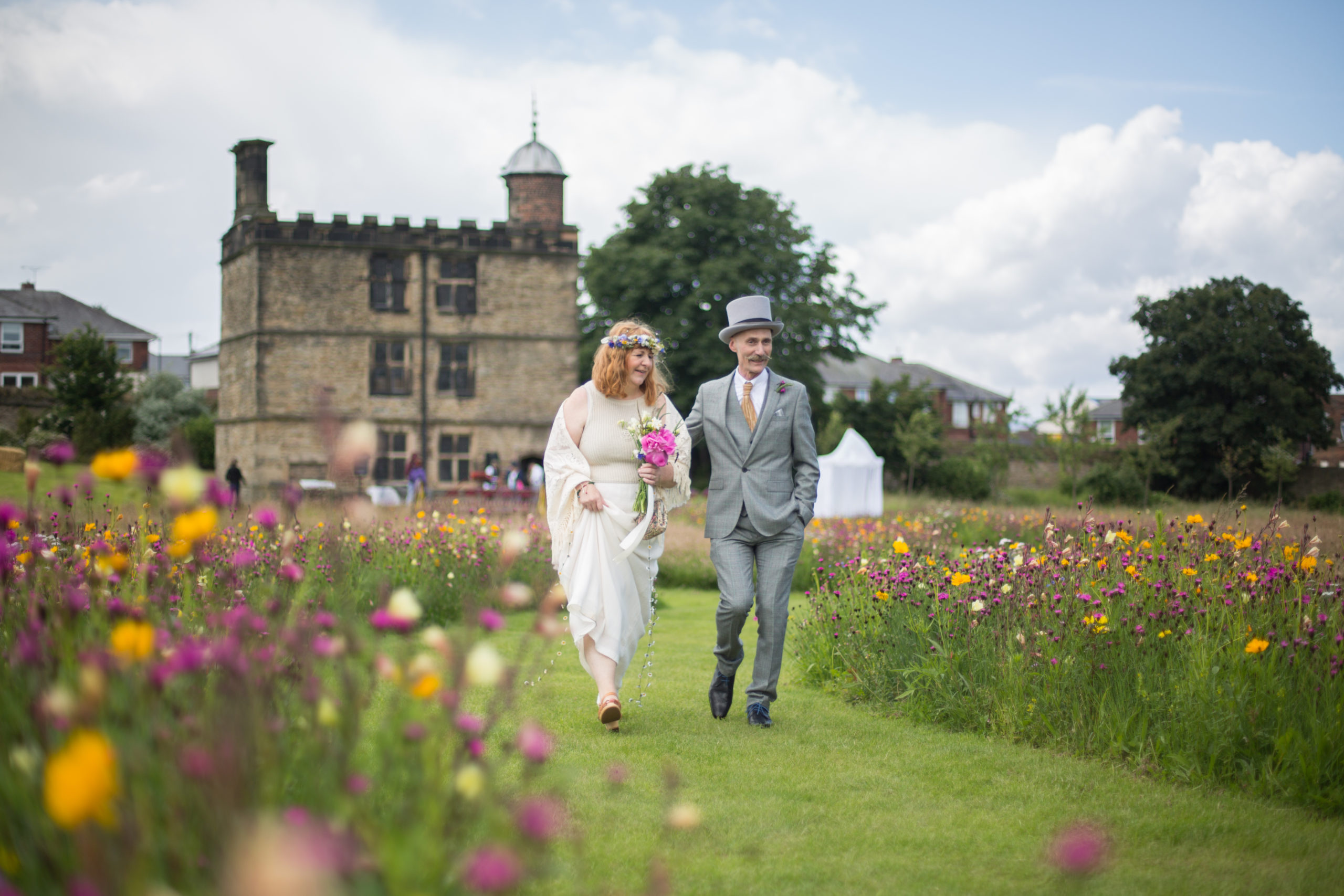 Bride and groom walk happily through pink and yellow meadows in front of Sheffield Manor Lodge's Turret House