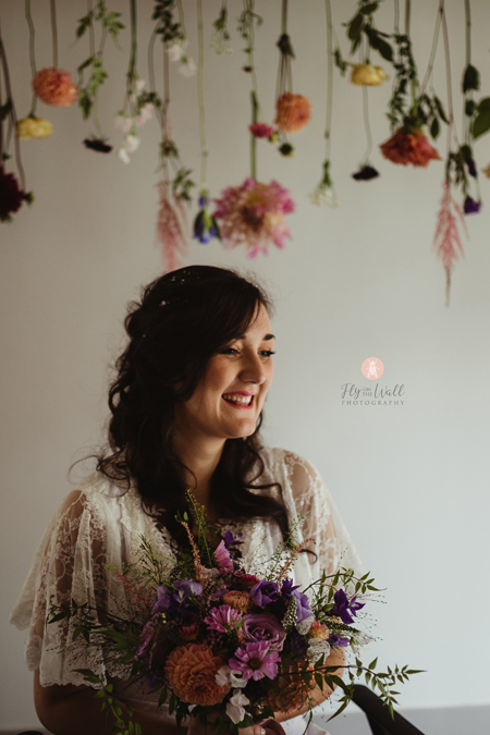 Fly on the wall photography - bride floral arch