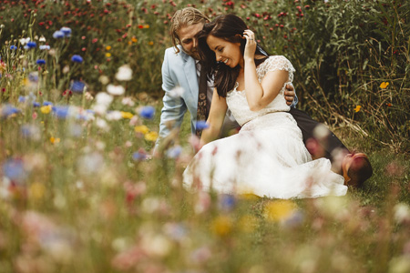 A bride and groom smile sat amongst the meadows at their sheffield manor lodge outdoor wedding