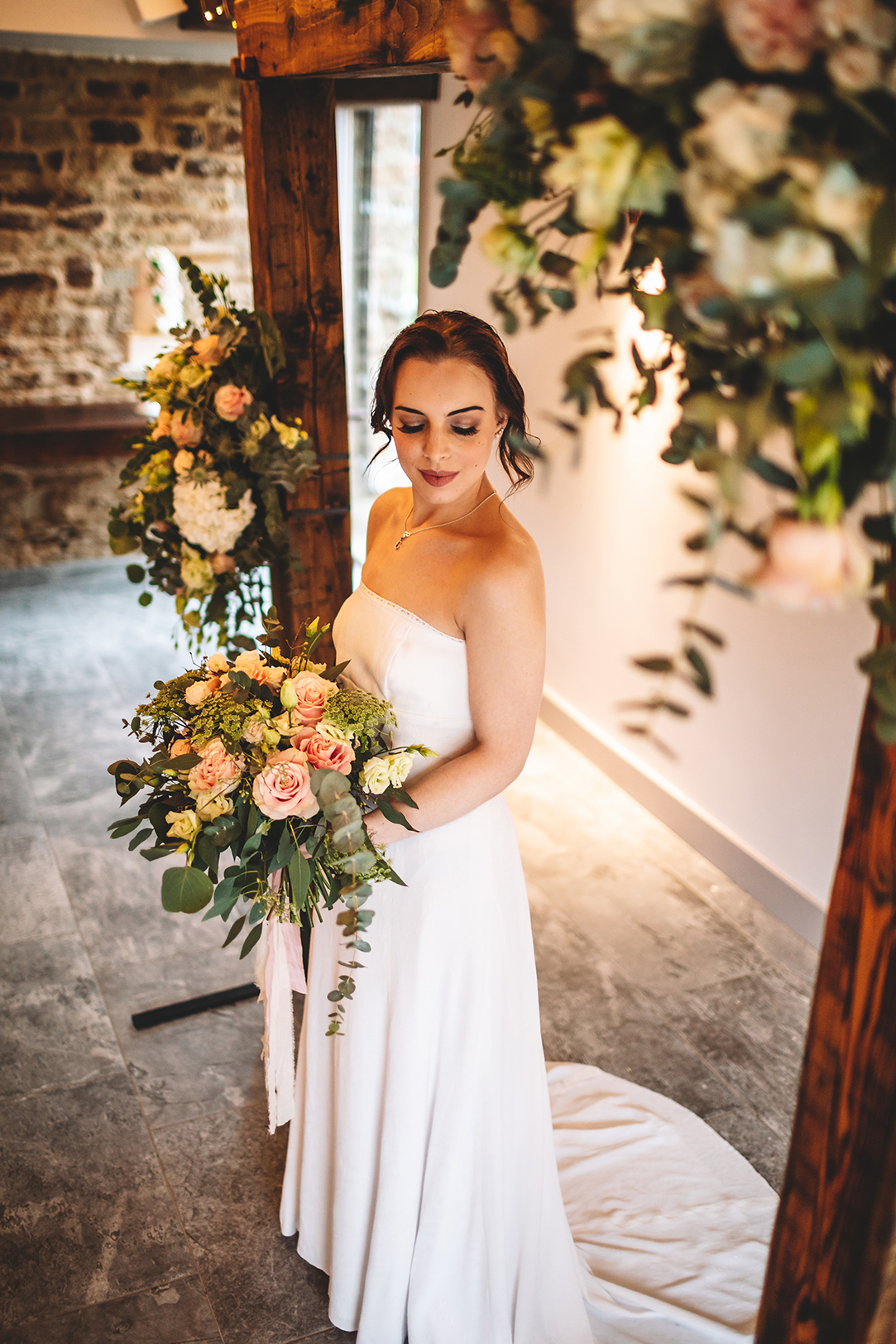 Bride stands under a rustic wooden arch decorated wthflowers in Manor Oaks House barn wedding venue