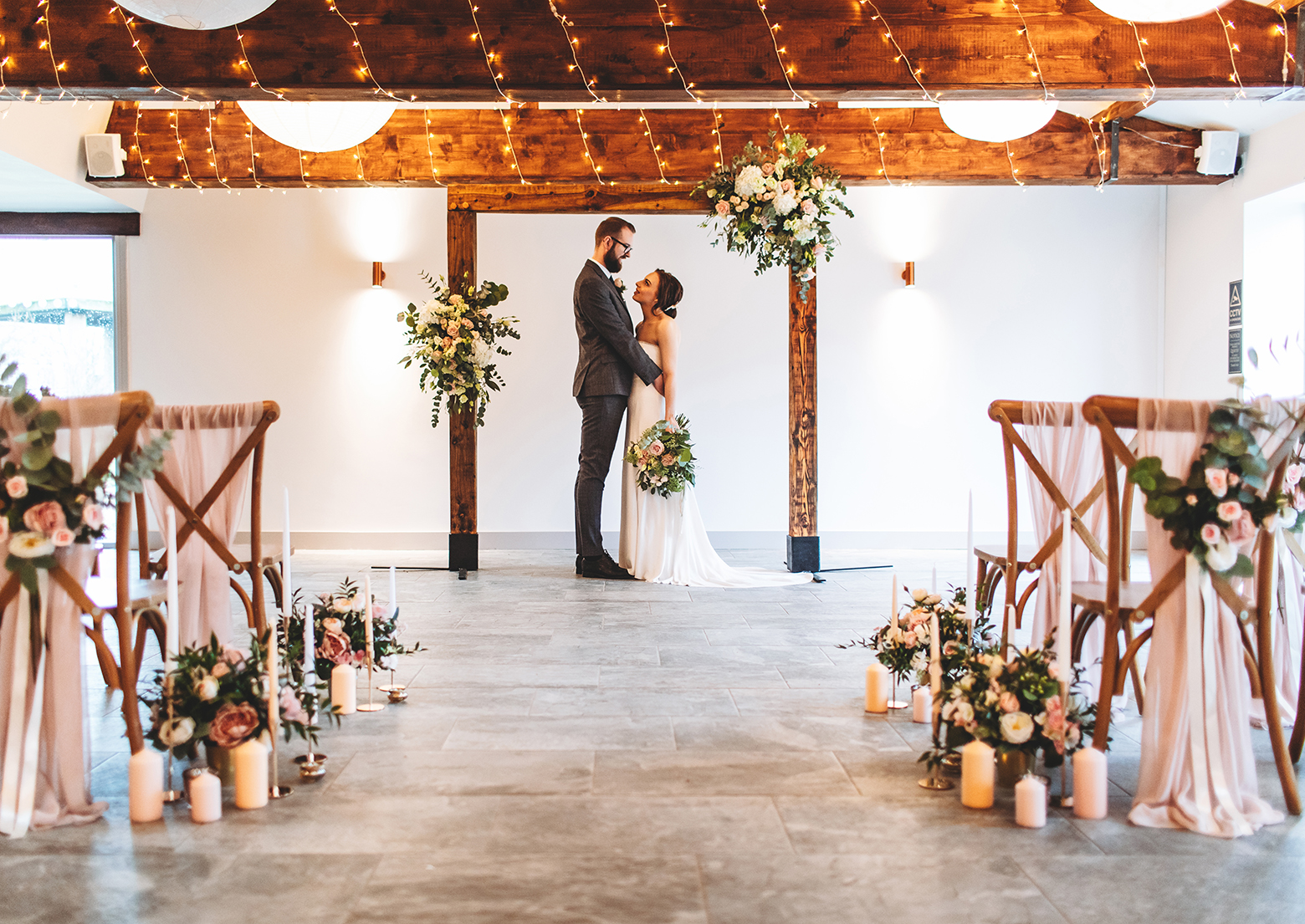 Bride and groom hold each other under a flowercovered rustic archway at their barn wedding ceremony.