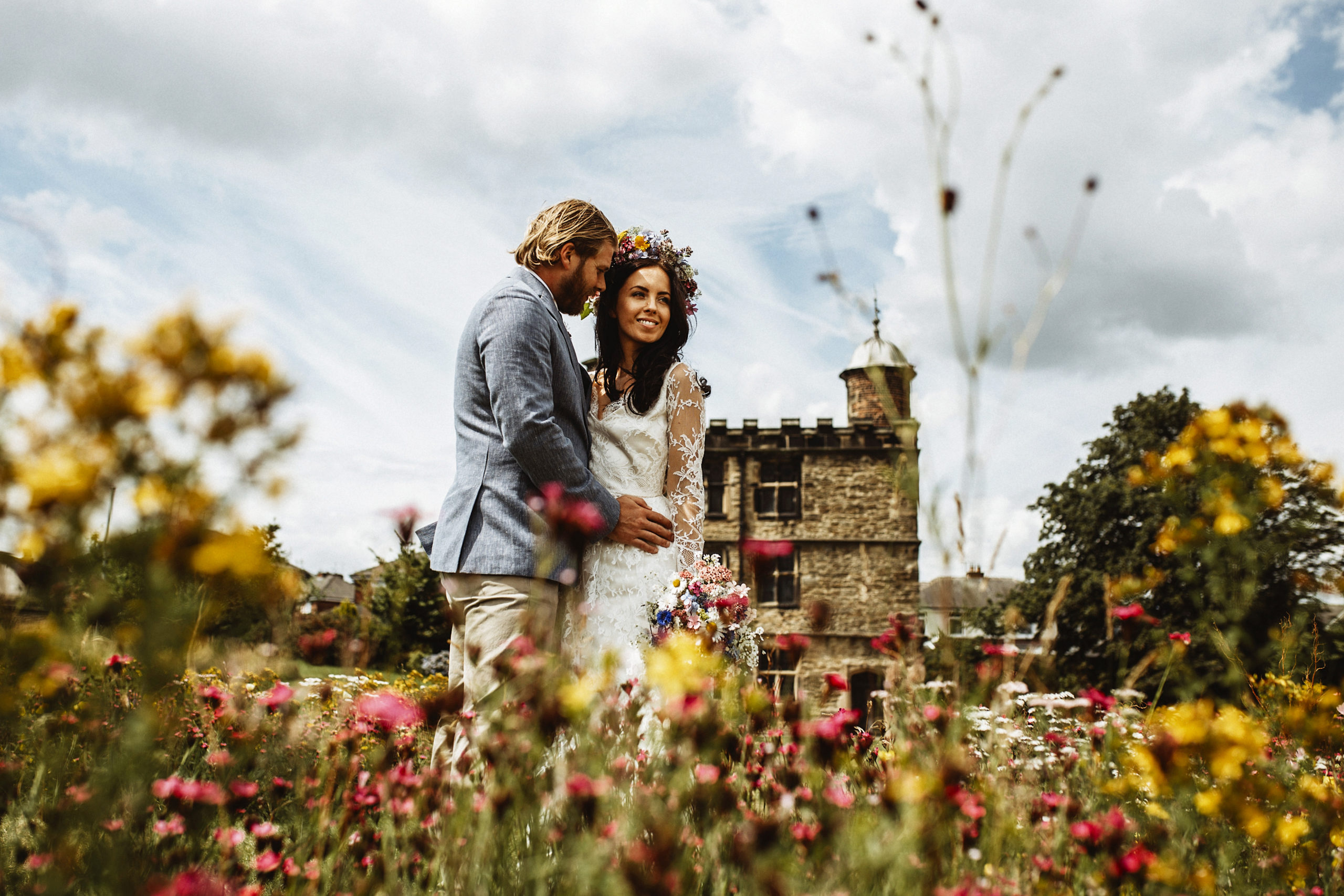 A bride and groom stood in front of Sheffield Manor Lodge Turret House surrounded by meadows at their wedding