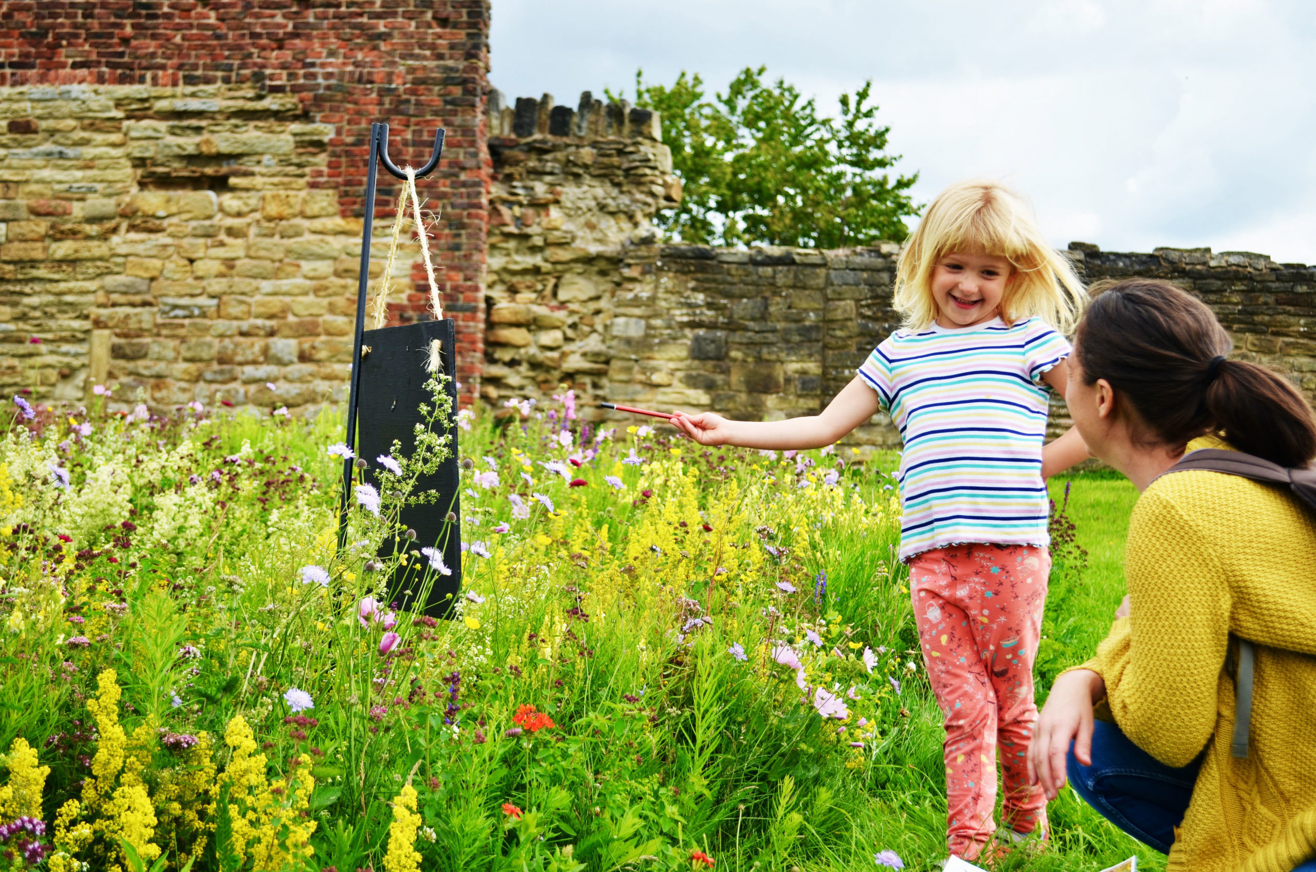Child running through meadows towards mum as she explores the ruins on a nature trail