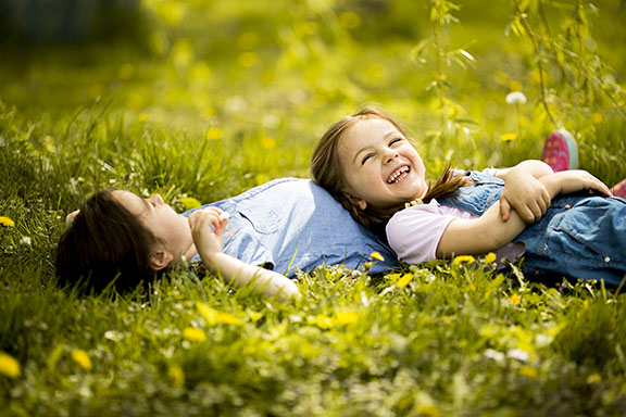Girls lying in the grass smiling in the sunshine